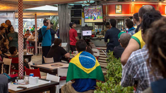 People watch a Brazilian athlete win gold on the television in a beachside cafe at Copacabana Beach on August 8, 2016 in Rio de Janeiro, Brazil.