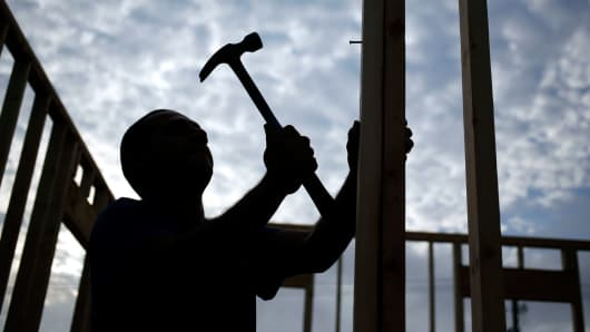 The silhouette of a contractor is seen hammering wood framing for a house under construction in the Norton Commons subdivision of Louisville, Kentucky.