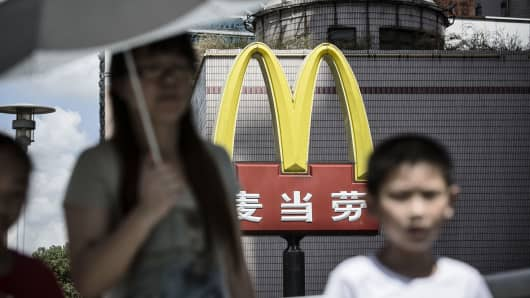 Pedestrians walk past a sign for McDonald's in Shanghai, China.