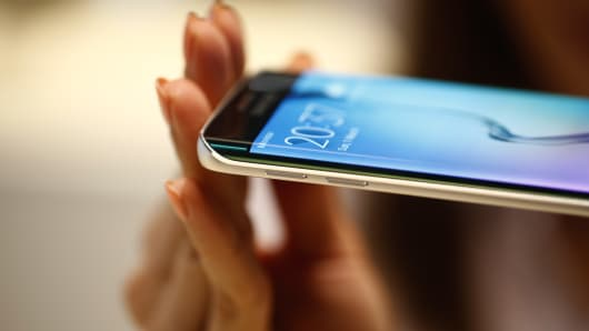 An employee shows the curved screen of a new Galaxy S6 Edge smartphone device