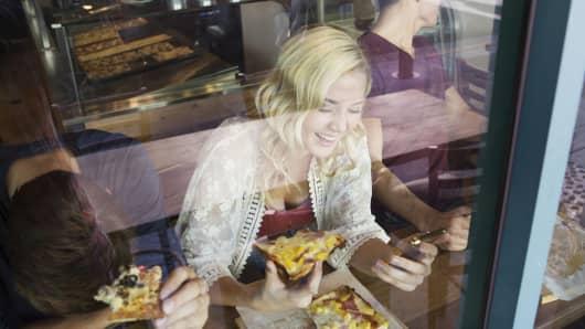 Millennial eating artisanal pizza