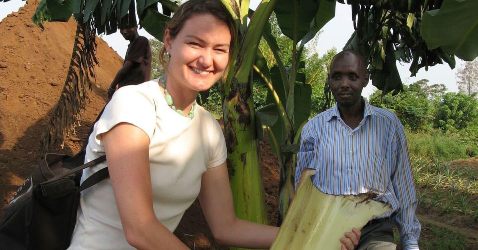 Elizabeth Scharpf holding a banana tree trunk.