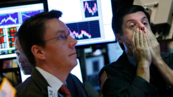 A trader rubs his face while working on the floor of the New York Stock Exchange October 7, 2008 in New York City.