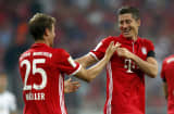 Robert Lewandowski (R) of Bayern Muenchen celebrates scoring his team's third goal with his team mate Thomas Mueller