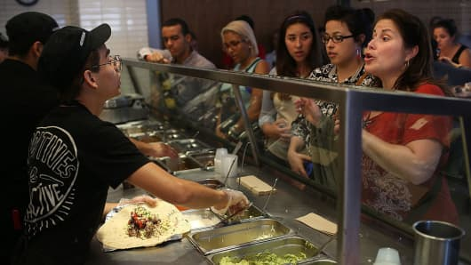 Chipotle restaurant workers fill orders for customers.
