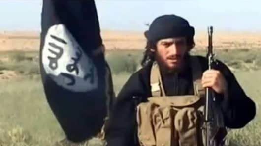 Abu Mohammad al-Adnani speaking next to an Islamist flag at an undisclosed location.
