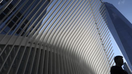 A man walks past the exterior of the Oculus Transit Hub and One World Trade Center