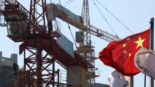 A Chinese flag flies in front of cranes at a construction site in the Fun City apartment complex, developed by China Vanke Co., in the Fangshan district of Beijing, China.