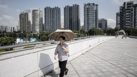 A woman holding an umbrella walks on an overpass in front of residential buildings in Shenzhen, China, on August 23, 2016.