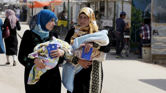 Syrian refugee women carry their babies as they walk through Al Zaatari refugee camp in the Jordanian city of Mafraq, near the border with Syria March 8, 2016.