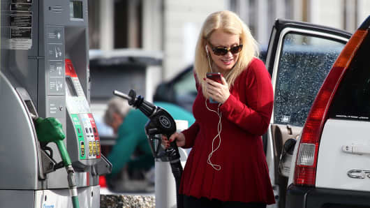 A customer prepares to pump gasoline into her vehicle at a Chevron gas station in San Rafael, California.