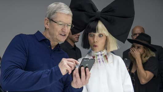 Tim Cook, chief executive officer of Apple, left, holds an iPhone 7 Plus while speaking with dancer Maddie Ziegler during an event in San Francisco.