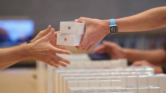 An Apple employee hands over Apple iPhone 7 phones on the first day of sales of the new phone at the Berlin Apple store on September 16, 2016 in Berlin, Germany.