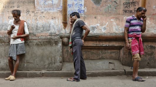 Labourers speak on mobile phones opposite a public call office (PCO) in a market area in Kolkata, India, March 9, 2016.