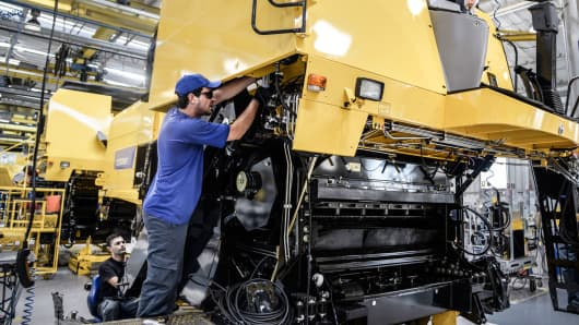 Workers assemble a grain combine at the Case New Holland factory in Curitiba, Brazil.