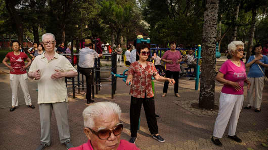 Elderly Chinese men and women take part in morning exercises in Beijing, China.