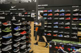 An employee carries Nike Inc. sneakers for a customer at a Dick's Sporting Goods Inc. store in Sterling Heights, Michigan.
