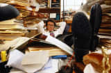 Businessman with books on desk