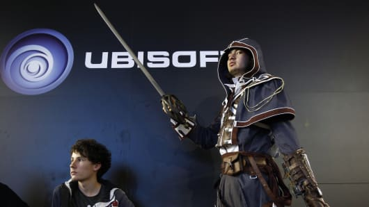 A visitor dressed in a costume of Dorian Arno, a character from 'Assassin's Creed Unity,' poses in front of a Ubisoft logo during the Paris Games week, a trade fair for video games, on October 29, 2015, in Paris.