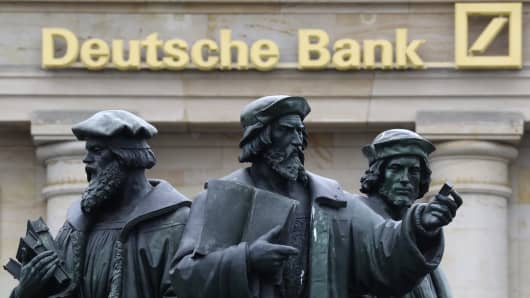 A statue is pictured next to the logo of Germany's Deutsche Bank in Frankfurt, Germany, September 30, 2016.