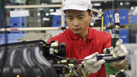 A worker assembles parts to make engines at Nissan Motor's plant in Yokohama, Japan.