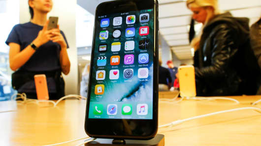 Customers look at the iPhone 7 smartphone inside an Apple store in New York.