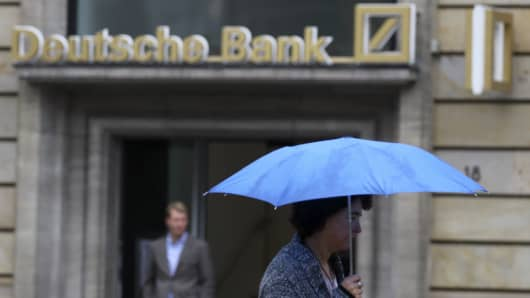 A woman with umbrella walks past a Deutsche Bank branch in Frankfurt, Germany, September 30, 2016.