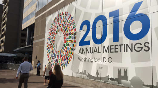 Pedestrians walk past a sign for the IMF Annual Meeting in Washinton, D.C. on Oct. 4, 2016.