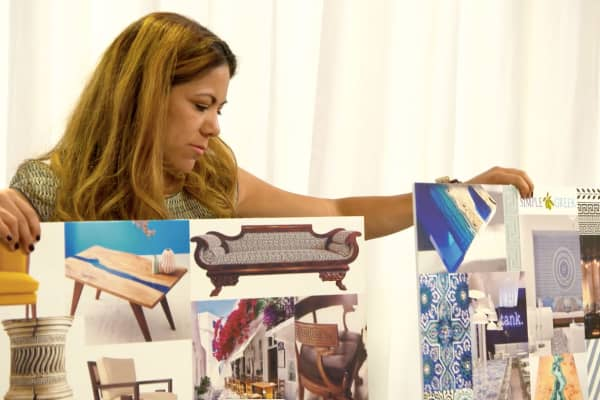 Ana Martinez, co-owner of Pacific Hospitality Design, an L.A.-based family furniture business, showcases her mood boards as part of her pitch to design furniture for The Simple Greek.