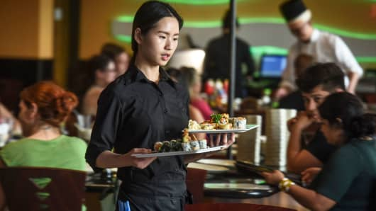 A waitress delivers sushi orders at Masa Hibachi Steakhouse & Sushi in Silver Spring, Maryland.