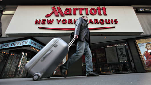 A pedestrian pulls luggage behind him as he walks outside a Marriott hotel in New York.