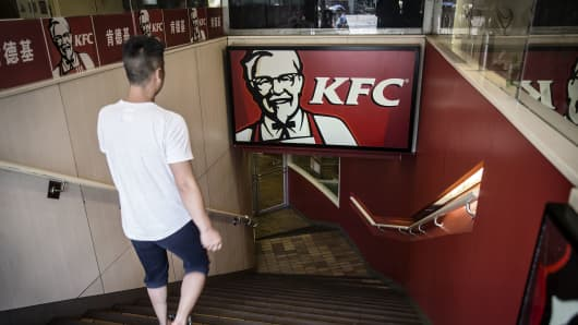 A man walks towards a Yum! Brands Inc. KFC restaurant in Shanghai, China.