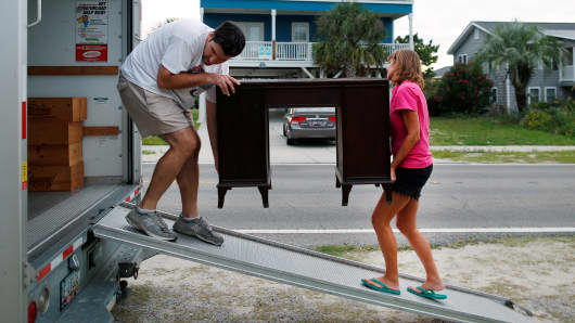 Dean Legge (L) helps his sister-law Josey Vereen (R) remove furniture from the lower level of her beachfront home along Waccamaw Drive in anticipation of Hurricane Matthew in Garden City Beach, South Carolina, U.S. October 4, 2016.