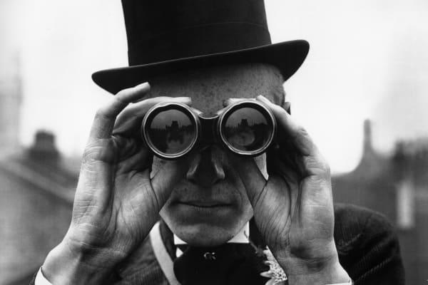 Man in top hat with binoculars, wealth