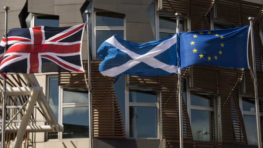 A Scottish Saltire (C) flies between a Union flag (L) and a European Union (EU) flag in front of the Scottish Parliament building in Edinburgh.