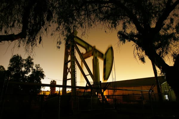Pumps draw petroleum from oil wells through the night