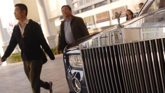 Pedestrians walk past a Rolls Royce parked in front of a Beijing hotel.