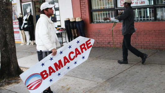 A person holds a sign directing people to an insurance company where they can sign up for the Affordable Care Act, also known as Obamacare.