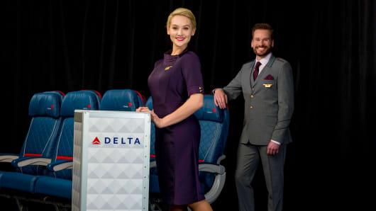 "Delta flight attendants show off the airline's new ""Passport Plum"" uniforms designed by Zac Posen."