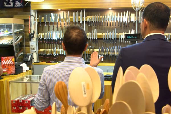 Marcus Lemonis and owner Howard Nourieli gaze upon the store's renovated knife wall.
