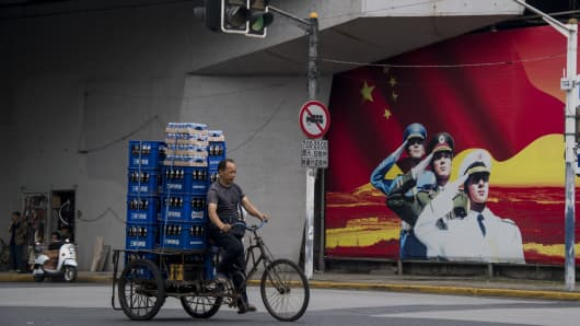 A man passes a military propaganda poster on a street in Shanghai, China.