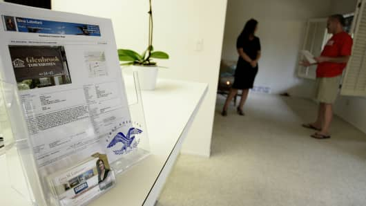 A display for a realtor with Coldwell Banker Dynasty TC, left, is displayed as she speaks with a potential homebuyer during an open house in Arcadia, California.