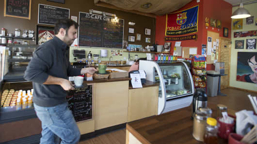 Jordi Carbonell, owner of the Cafe Con Leche coffee shop, brings an order to customers at the shop in the Mexicantown neighborhood of Southwest Detroit, Michigan.
