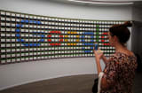 A woman takes pictures of a sign after the opening of Google's pop-up store in New York