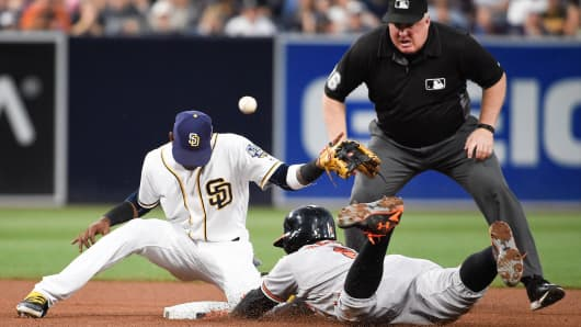 Jonathan Schoop, #6 of the Baltimore Orioles, slides into second base with a double as Alexei Ramirez, #10 of the San Diego Padres, misses the throw while umpire Bill Miller looks on during the fourth inning of a baseball game at Petco Park on June 28, 2016, in San Diego, California.