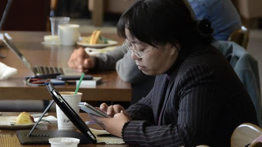 Woman on a cell phone while in front of a tablet
