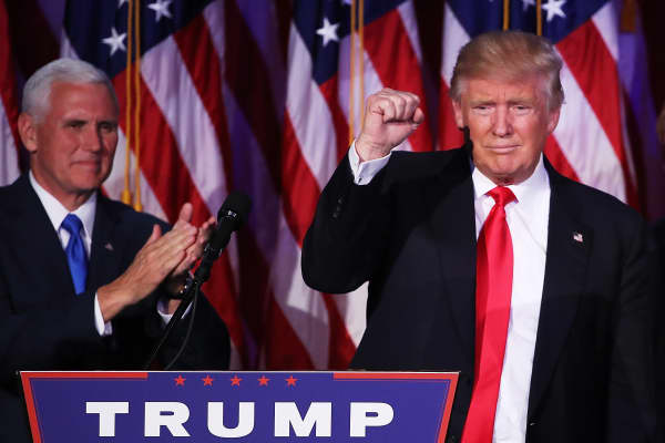 Republican president-elect Donald Trump acknowledges the crowd as Vice president-elect Mike Pence looks on during his election night event at the New York Hilton Midtown in the early morning hours of November 9, 2016 in New York City.