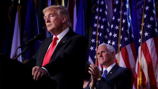 Republican president-elect Donald Trump delivers his acceptance speech as Vice president-elect Mike Pence looks on during his election night event.