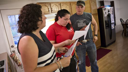A realtor, left, speaks with potential home buyers as they tour a home for sale in Sparland, Illinois,