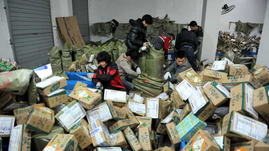 Chinese workers sort through boxes of goods at a delivery company in Lin'an, east China's Zhejiang province on November 11, 2016.